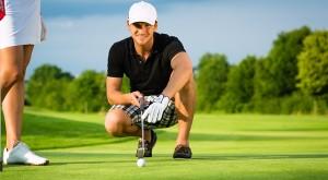 Junger Golf Spieler am Golfplatz beim Einlochen